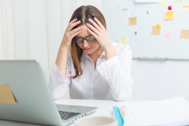 Mujer cansada en el trabajo en la computadora. dolor de cabeza. Foto Premium