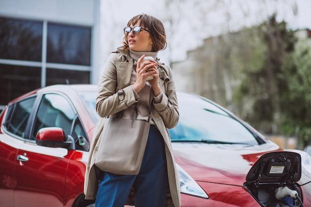 Mujer cargando un coche eléctrico en la gasolinera eléctrica y tomando café Foto gratis
