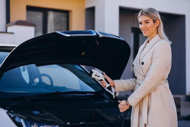 Mujer cargando electro car por su casa y sosteniendo el cargador Foto gratis