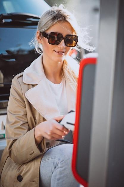 Mujer cargando electro coche en la gasolinera eléctrica Foto gratis