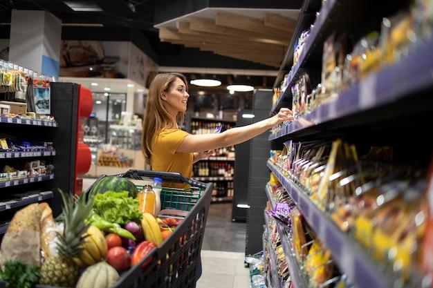 Mujer con carrito de compras comprando alimentos en el supermercado Foto gratis
