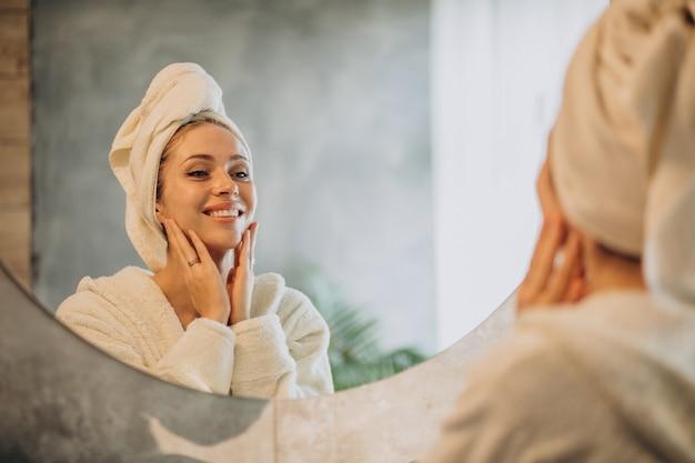 Mujer en casa aplicando mascarilla crema Foto gratis