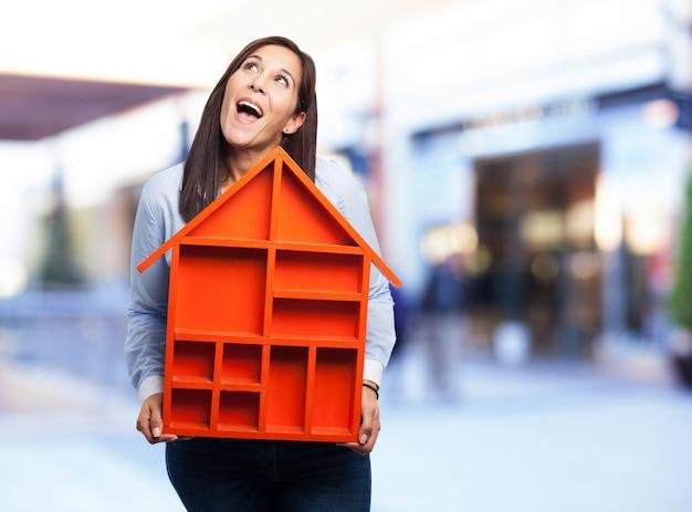 Mujer con una casa roja pequeña Foto gratis