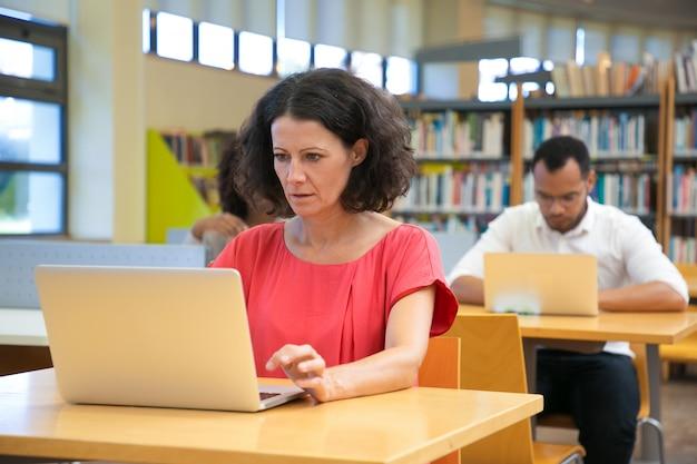 Mujer caucásica enfocada mirando portátil mientras está sentado en la mesa Foto gratis