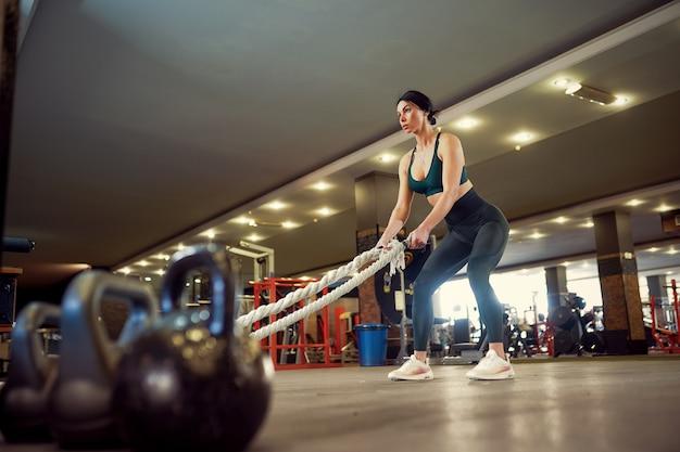 Mujer caucásica en forma vestida con ropa deportiva preparándose para el entrenamiento con cuerdas de batalla en el gimnasio Foto Premium