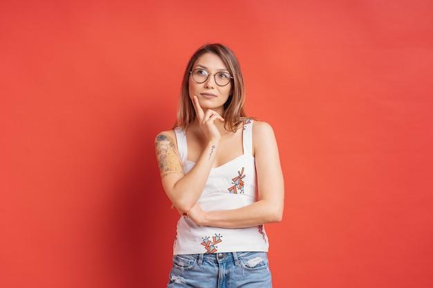 Mujer caucásica con gafas pensando e imaginación aislado en la pared roja Foto gratis