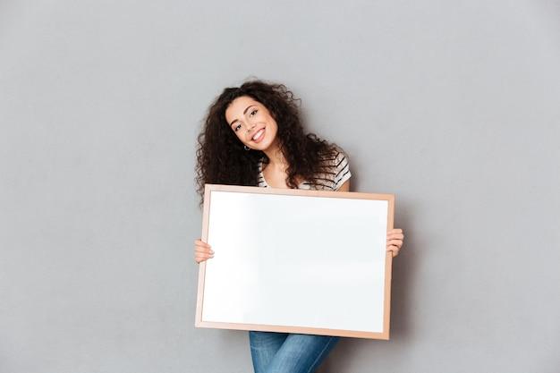Mujer caucásica con hermoso cabello posando sobre la pared gris con obras de arte en manos expresando admiración por el espacio de copia de retrato Foto gratis