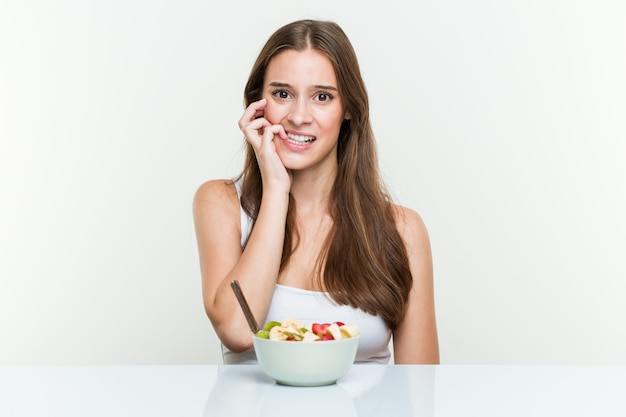 Mujer caucásica joven que come el tazón de fruta que muerde las uñas, nervioso y muy ansioso. Foto Premium