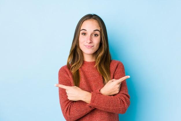 La mujer caucásica joven que presenta puntos aislados de lado, está intentando elegir entre dos opciones. Foto Premium