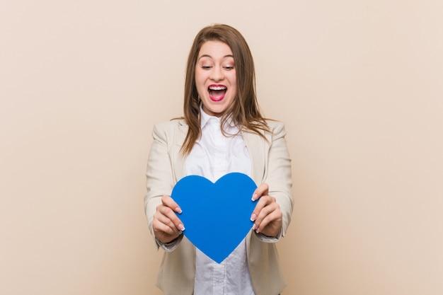 Mujer caucásica joven que sostiene un icono del corazón Foto Premium