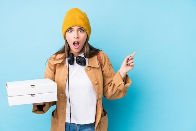 Mujer caucásica joven que sostiene las pizzas aisladas que señalan al lado Foto Premium