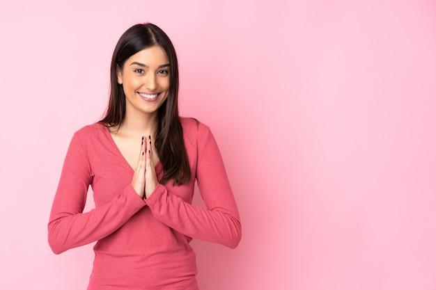 La mujer caucásica joven sobre la pared mantiene la palma junta. Foto Premium