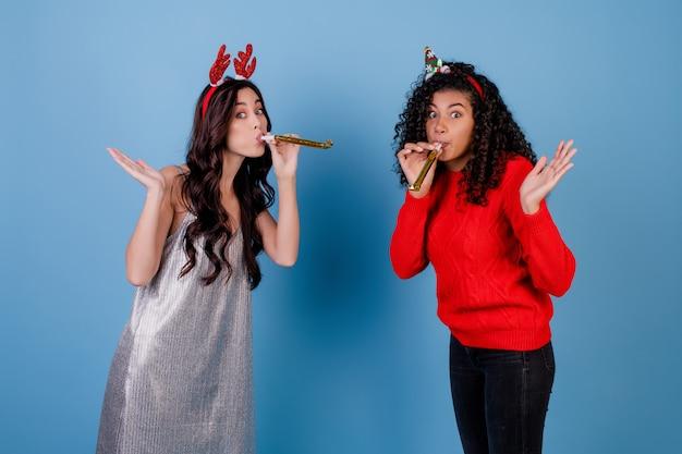 Mujer caucásica y niña negra soplando silbatos de navidad aislado sobre azul Foto Premium
