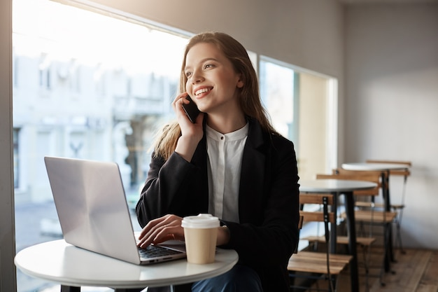 Mujer caucásica sentado en la cafetería con laptop, tomando café, hablando por teléfono inteligente Foto gratis