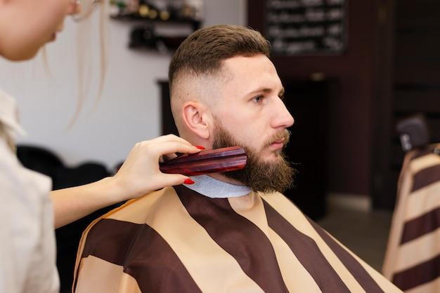 Mujer cepillando la barba de un hombre Foto gratis