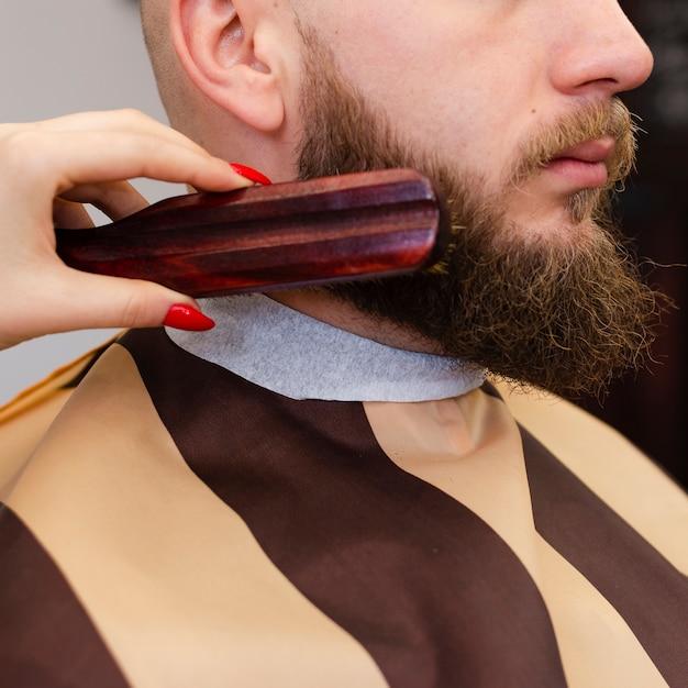 Mujer cepillando el primer plano de la barba de un hombre Foto gratis