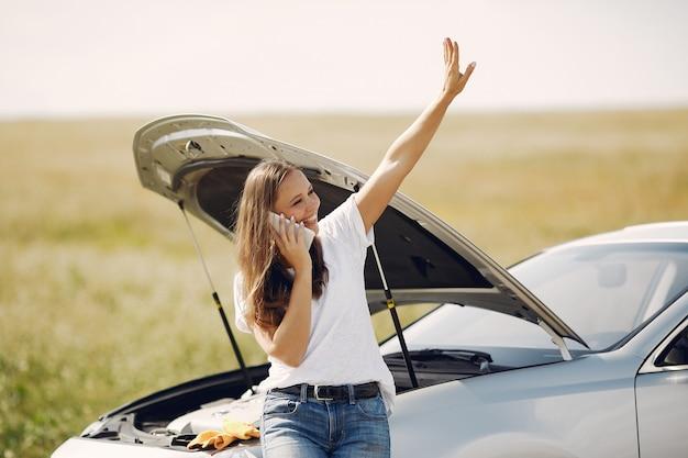 Mujer cerca de un auto roto pide ayuda Foto gratis