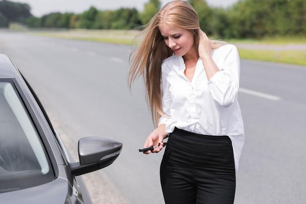 Mujer cerrando las puertas del auto Foto gratis