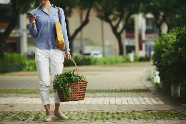 Mujer con cesta de comida fresca y teléfono inteligente de pie al aire libre Foto gratis