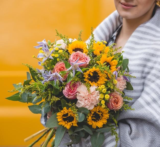 Mujer con chal sosteniendo un ramo de flores en fondo amarillo Foto gratis