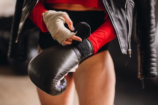 Mujer en chaqueta de cuero se pone guantes de boxeo Foto gratis