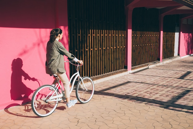 Mujer en una chaqueta monta una bicicleta de ciudad Foto Premium