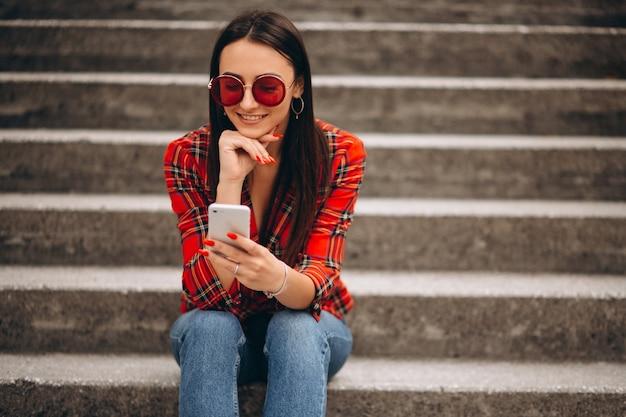 Mujer en la chaqueta roja que se sienta en las escaleras usando el teléfono Foto gratis