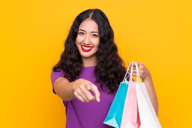 Mujer china española con bolsa de compras sobre pared aislada señala con el dedo con una expresión segura Foto Premium