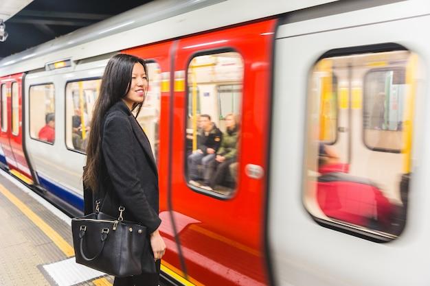 Mujer china esperando en la estación de metro Foto Premium