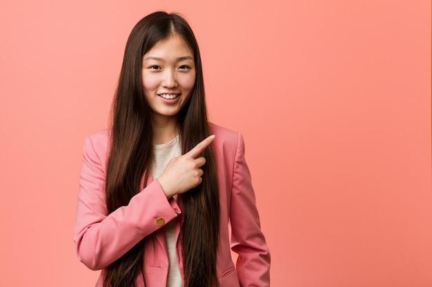 Mujer china del negocio joven que lleva el traje rosado que sonríe y que señala a un lado, mostrando algo en el espacio en blanco. Foto Premium