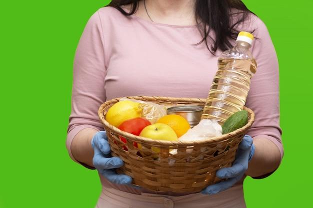 Mujer en un chromakey con una camiseta rosa y guantes médicos azules sostiene una canasta de donación con comida Foto Premium