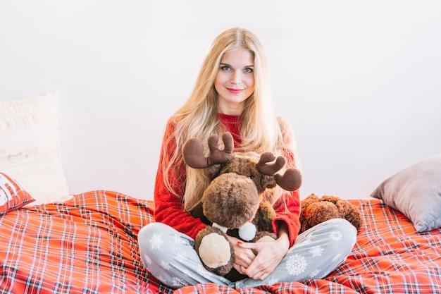 Mujer con ciervo de peluche mullido en cama Foto gratis