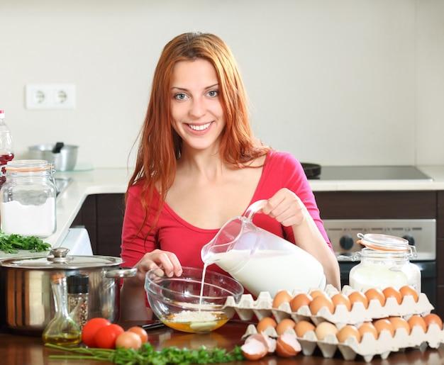 Mujer cocinando huevos revueltos en la cocina de casa for Cocinando en mi casa