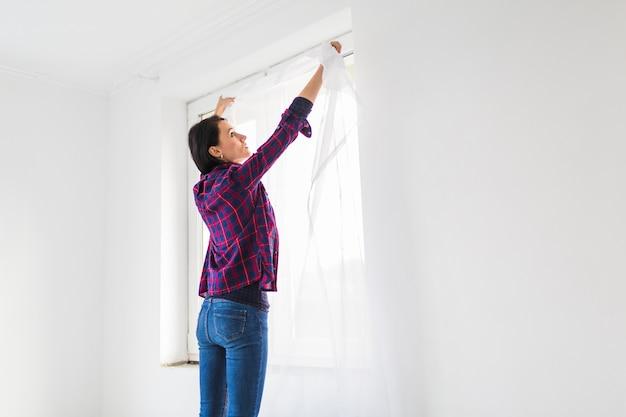 Mujer colgando cortinas en la ventana Foto gratis