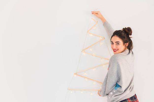 Mujer colgando de madera del árbol de navidad en la pared Foto gratis