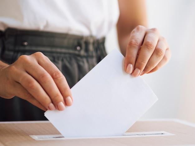 Mujer colocando boleta en caja Foto gratis