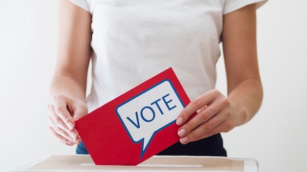 Mujer colocando tarjeta roja con mensaje de votación en un cuadro Foto gratis