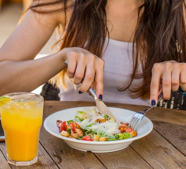 Mujer comiendo ensalada césar con un vaso de jugo de naranja fresco Foto gratis
