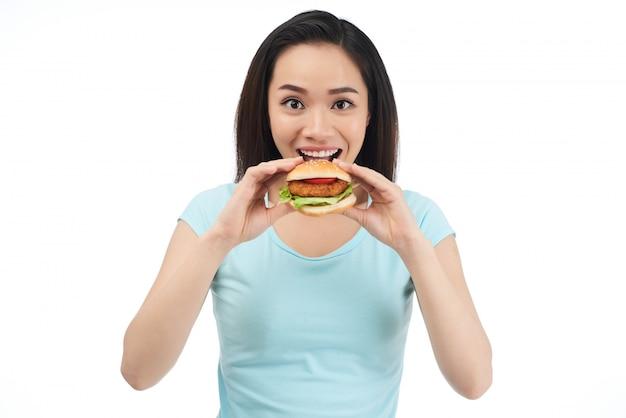 Mujer comiendo hamburguesa de pollo Foto gratis
