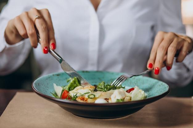 Mujer comiendo plato de ensalada Foto gratis