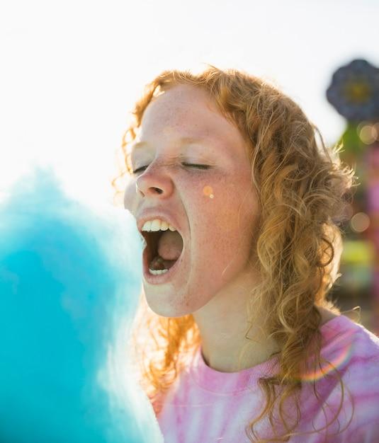 Mujer comiendo primer plano de algodón de azúcar Foto gratis