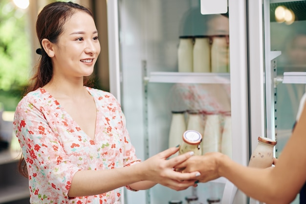 Mujer comprando yogur orgánico fresco Foto Premium
