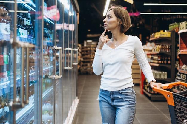 Mujer de compras en la tienda de comestibles, junto al refrigerador Foto gratis