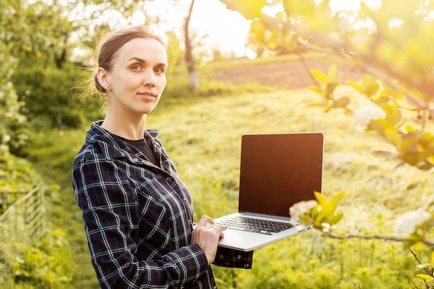 Mujer con una computadora portátil en la granja Foto gratis