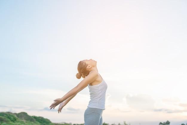 Mujer concentrada estirando sus brazos con el cielo de fondo Foto gratis
