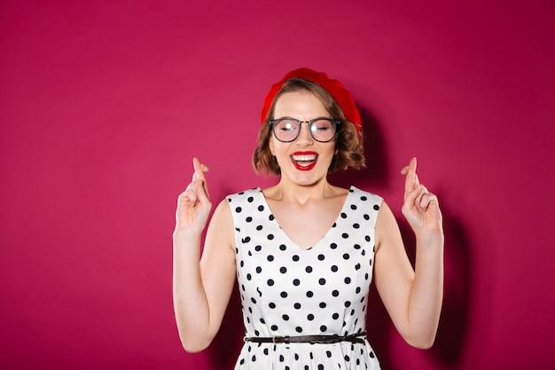 Mujer concentrada de jengibre con vestido y anteojos rezando con los dedos cruzados y los ojos cerrados sobre rosa Foto gratis