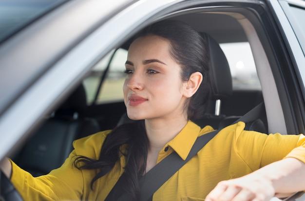 Mujer conduciendo en un día soleado Foto gratis