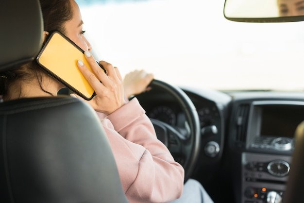 Mujer conduciendo y hablando por teléfono Foto gratis