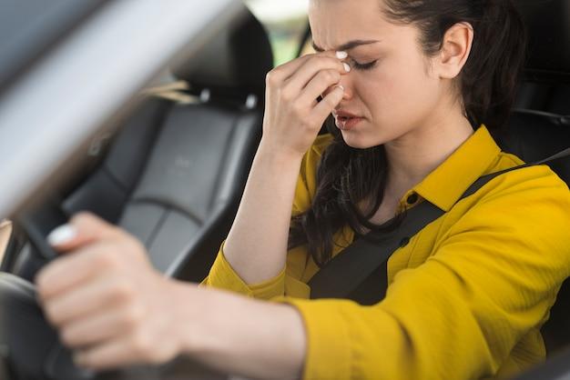 Mujer conduciendo y teniendo dolor de cabeza Foto gratis