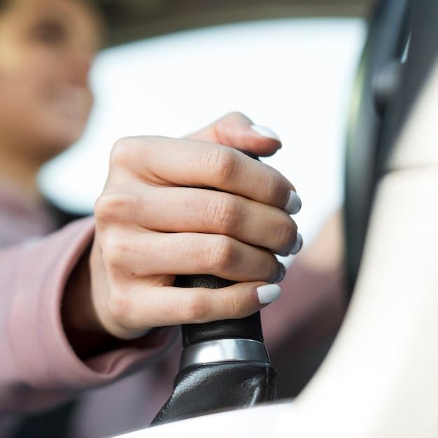Mujer conductora borrosa cambiando los engranajes Foto gratis